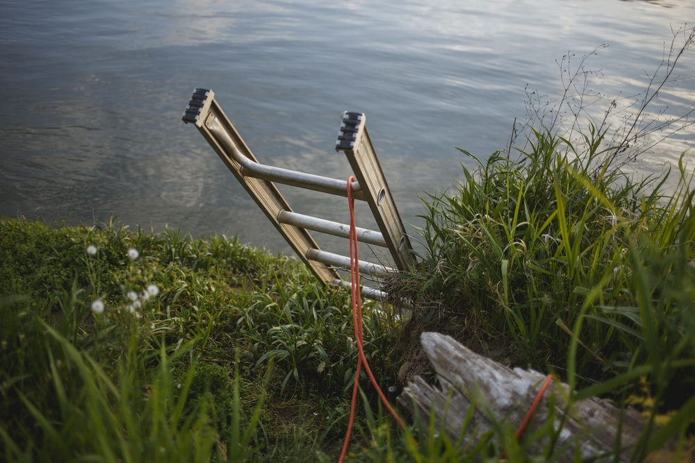 gray metal extension ladder on body of water leaning on soil surface