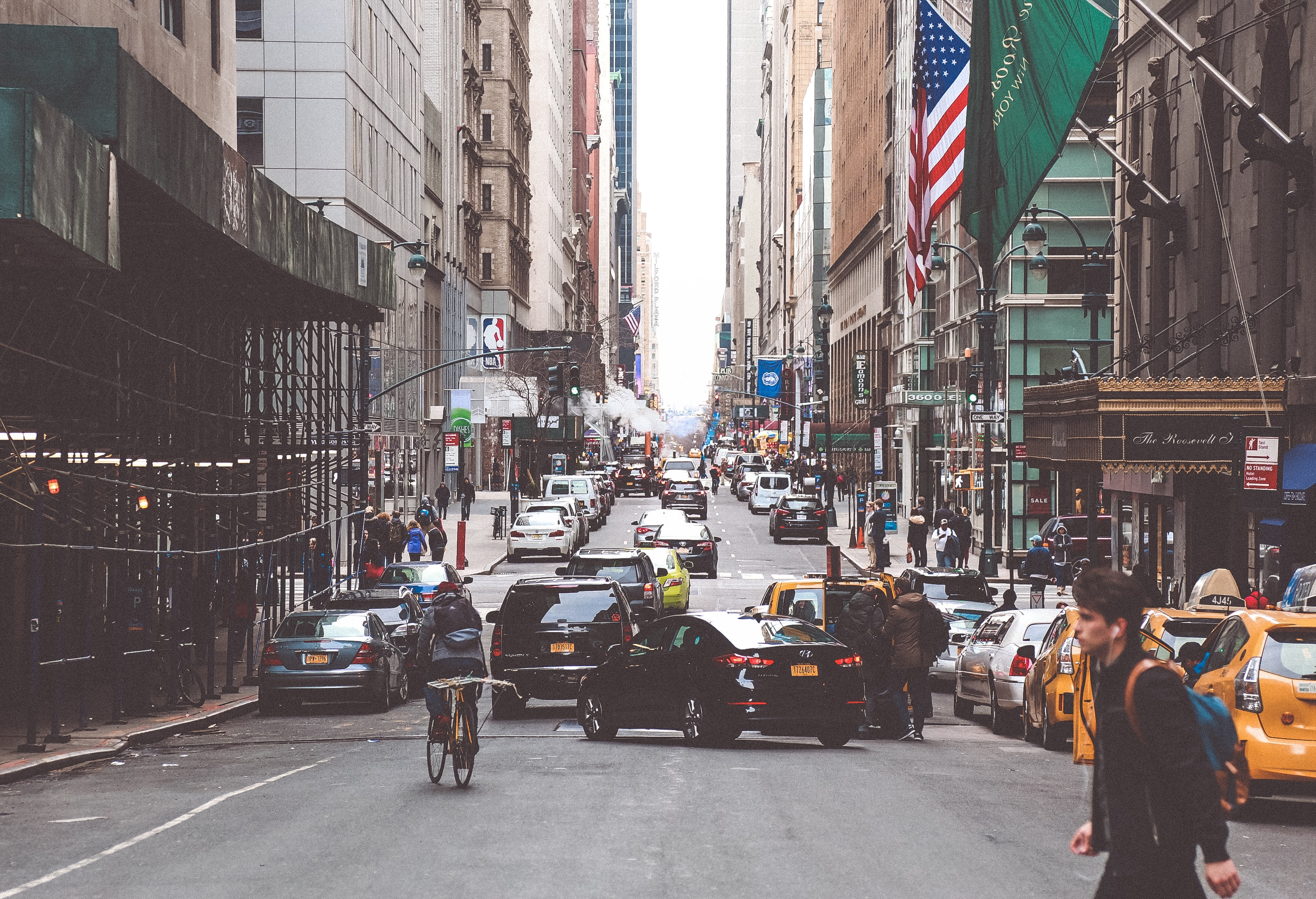man in black jacket crossing road during daytime