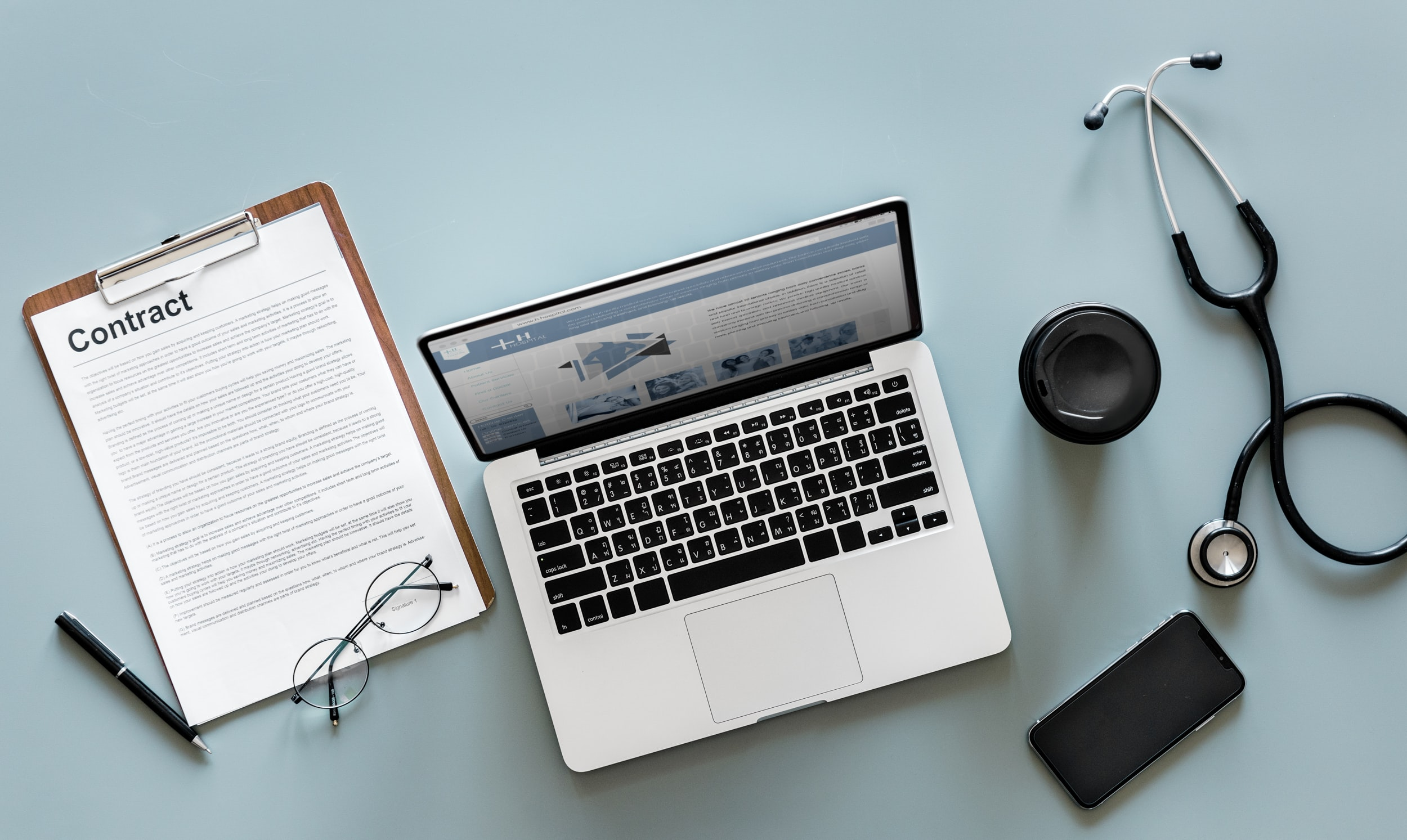 MacBook Pro near black stethoscope and brown clipboard