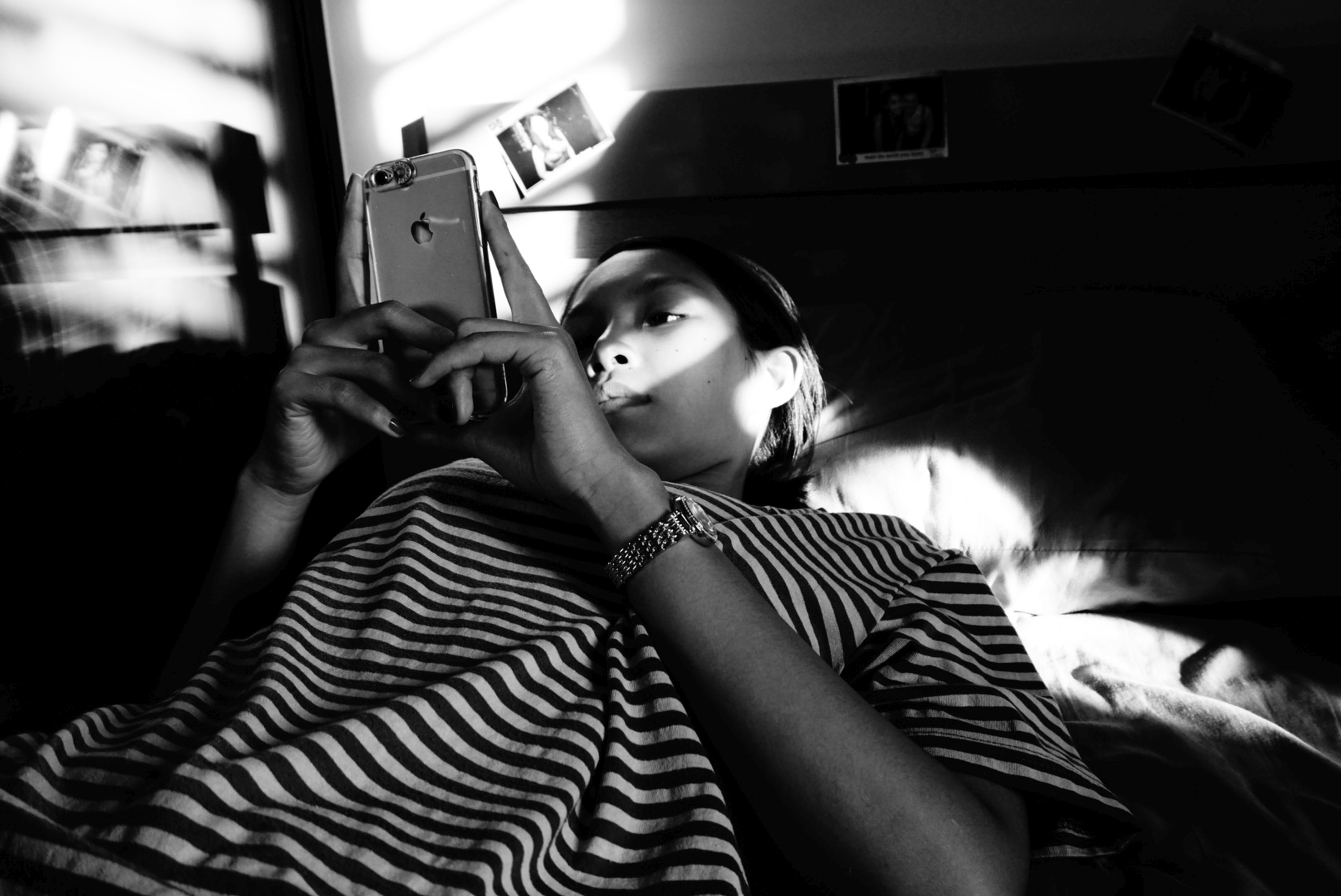 grayscale photography of woman wearing striped t-shirt holding iPhone 6 lying on bed