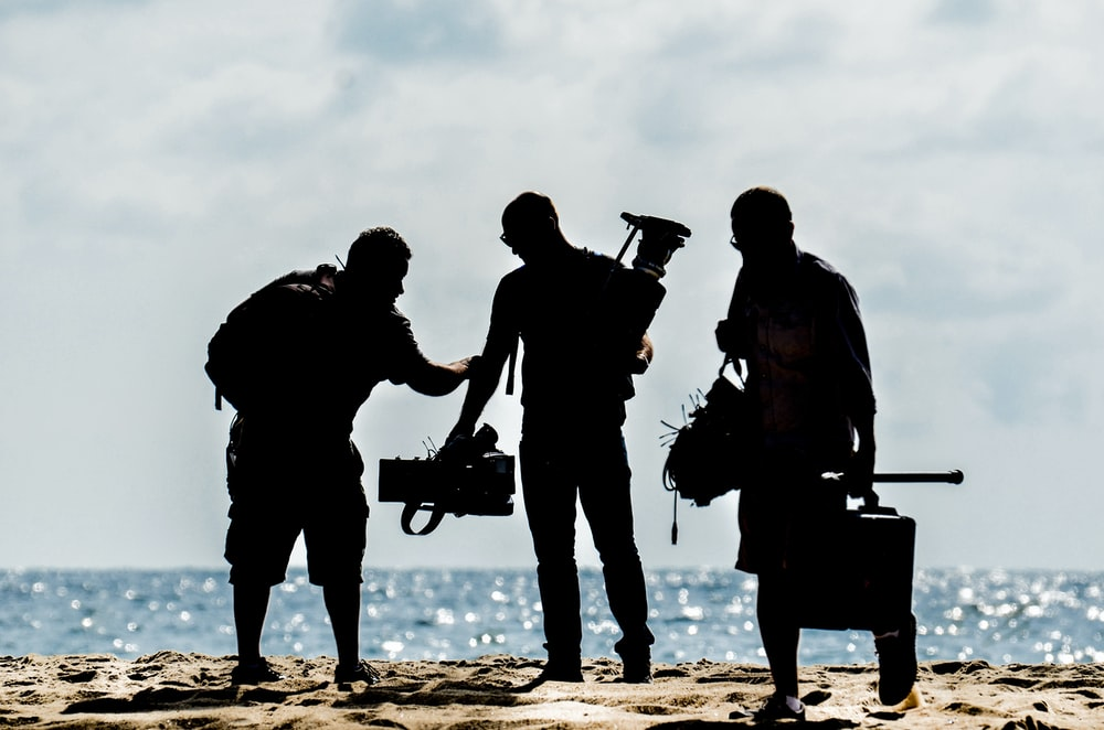 silhouette of men holding camera standing on sand near body of water during daytime