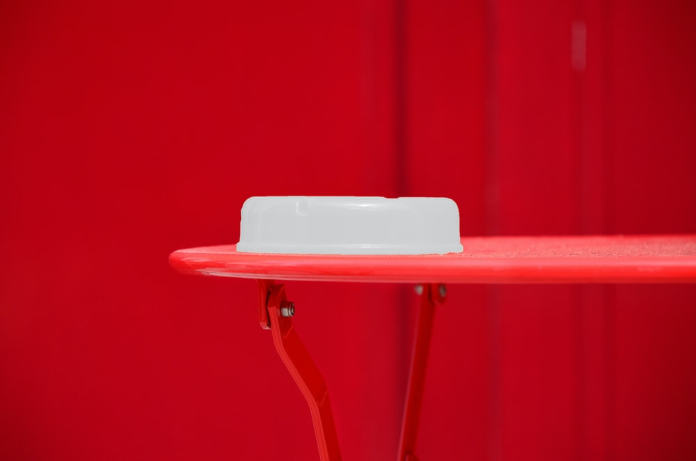 round white plastic container on red table