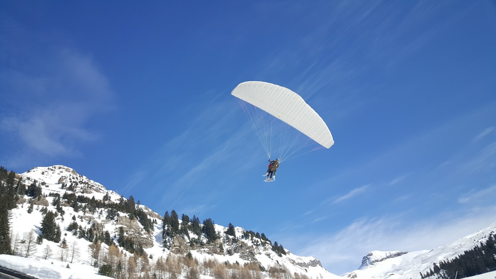 person using parachute near mountain