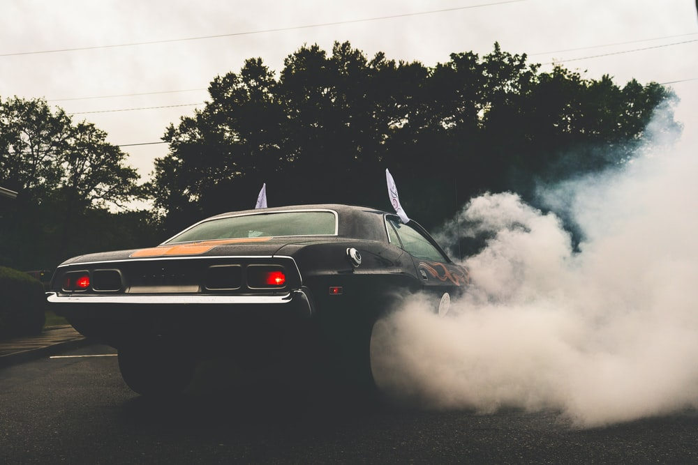 black coupe with wheels covered in smoke