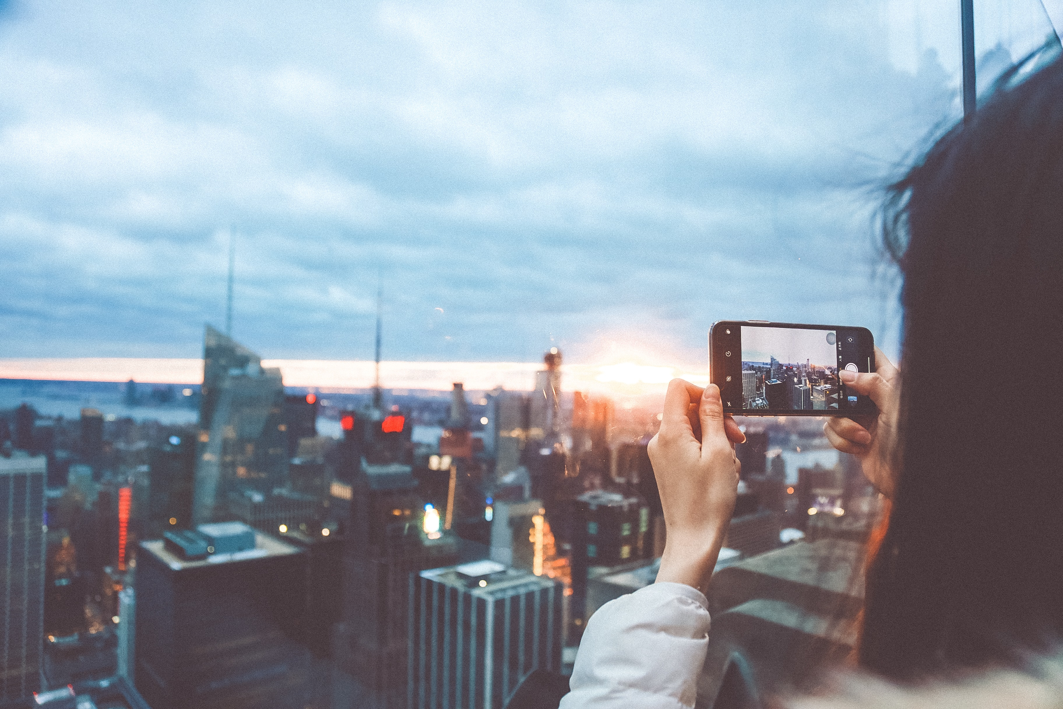 woman taking picture of high rise buildings