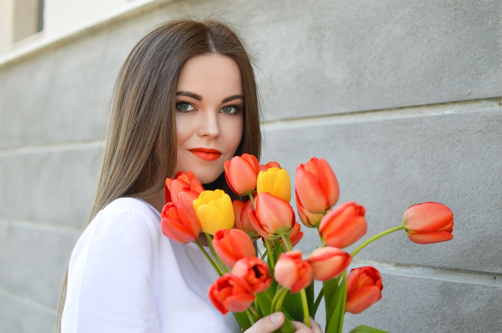 woman with bouquet of pink and yellow tulips