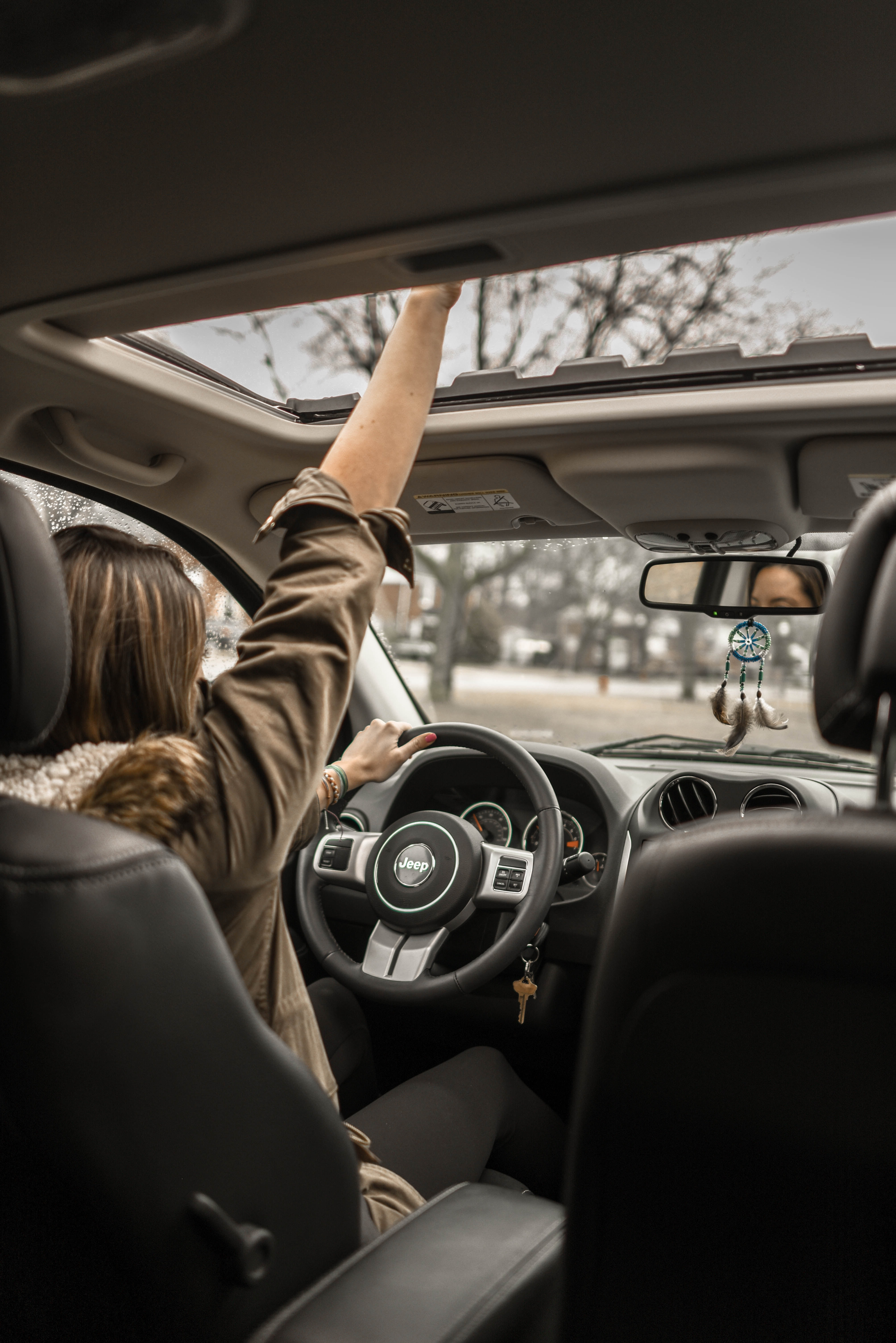woman raising her right hand inside black and brown vehicle