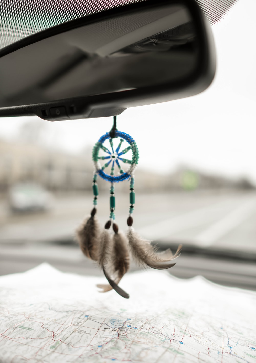 blue and green dream catcher hanging on black vehicle rear view mirror