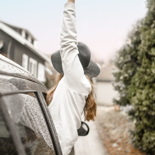 woman rising left hand on vehicle window during daytime