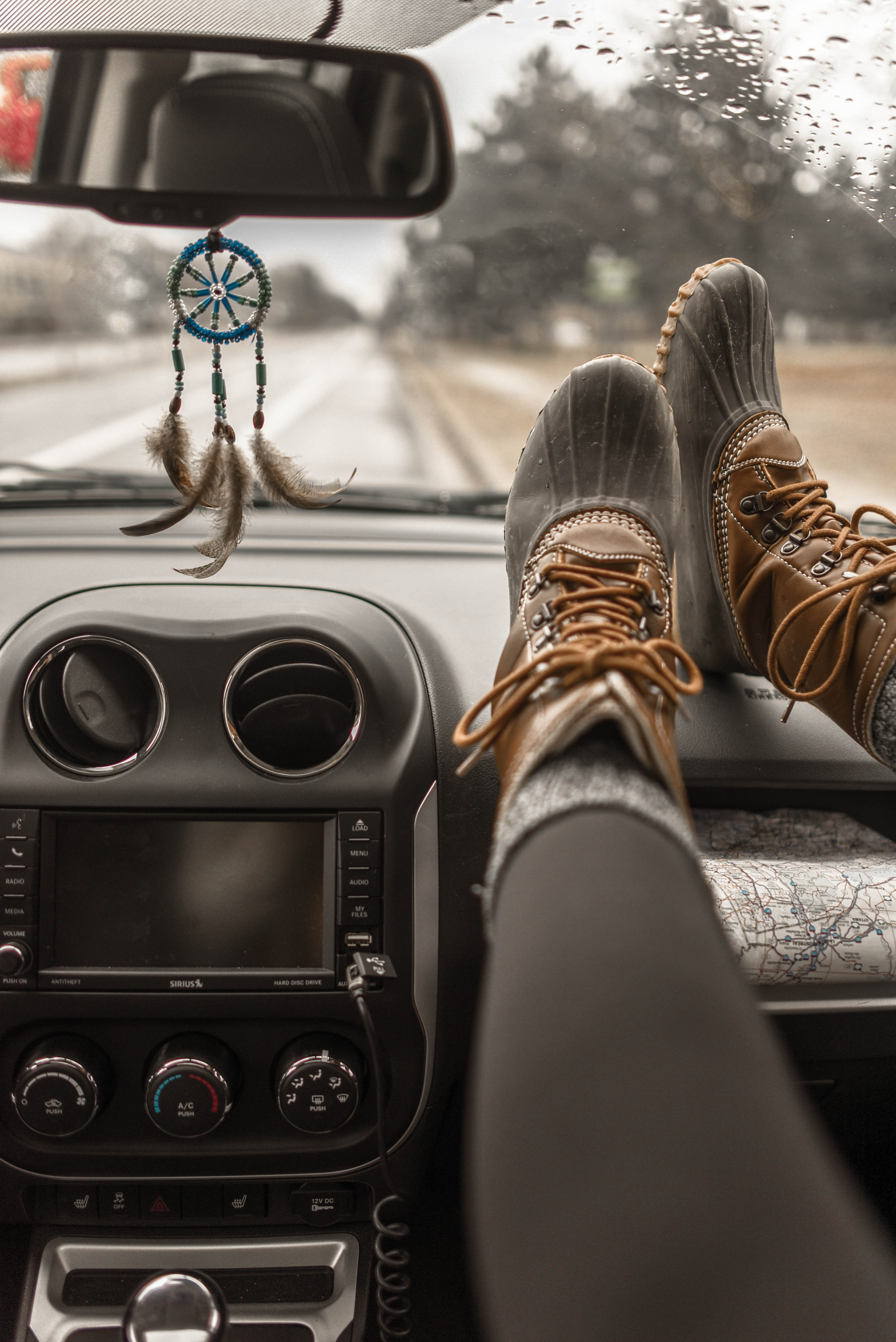 person wearing duck boots putting his boots on vehicle glove compartment