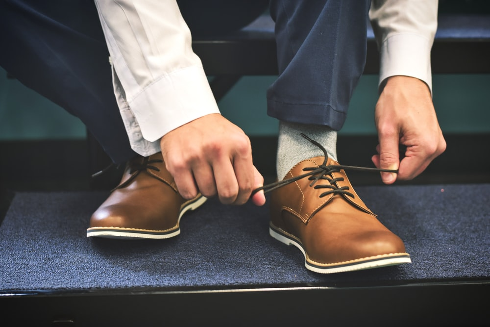 person tying brown leather shoes