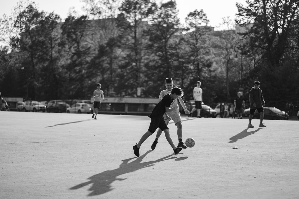 grayscale photo of group of man playing soccer on field