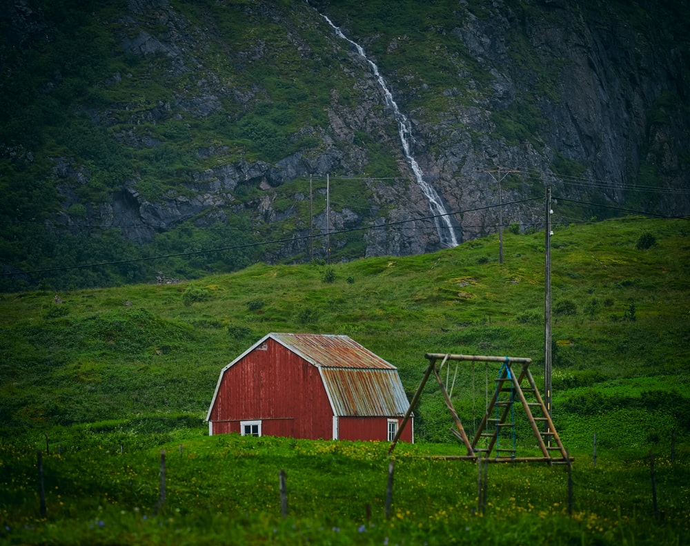 in distant photo of red barn on grass field