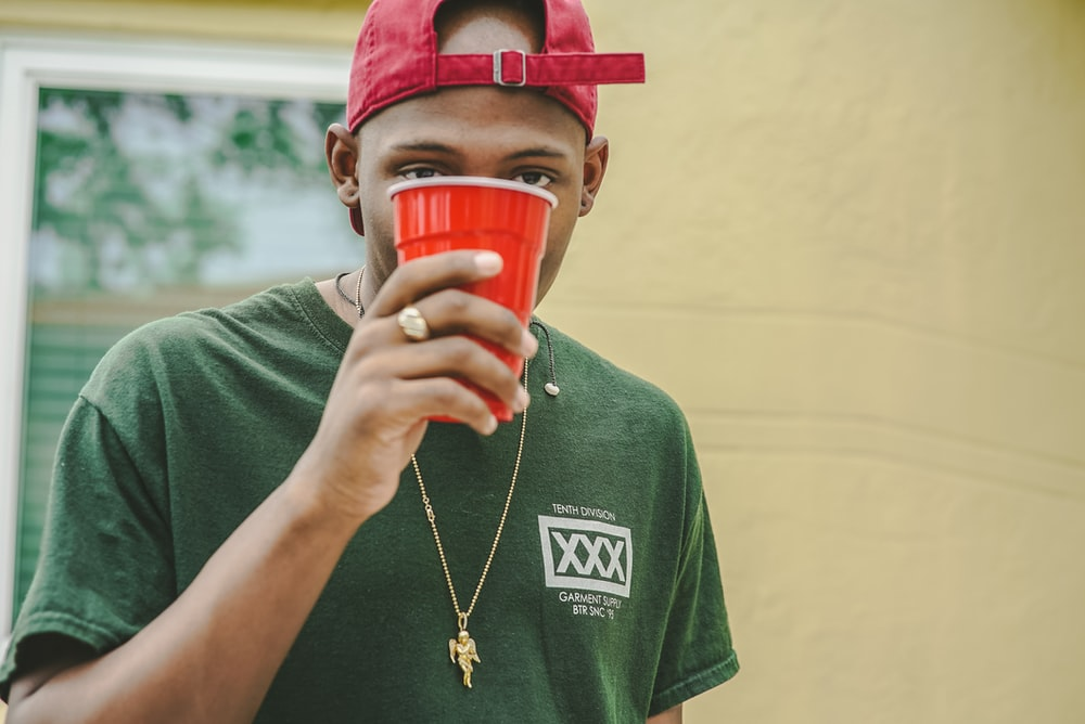 man holding red plastic cup