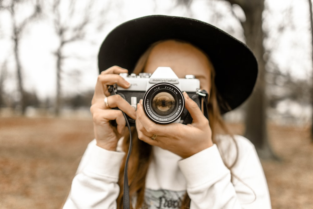 person holding camera taking picture to another camera