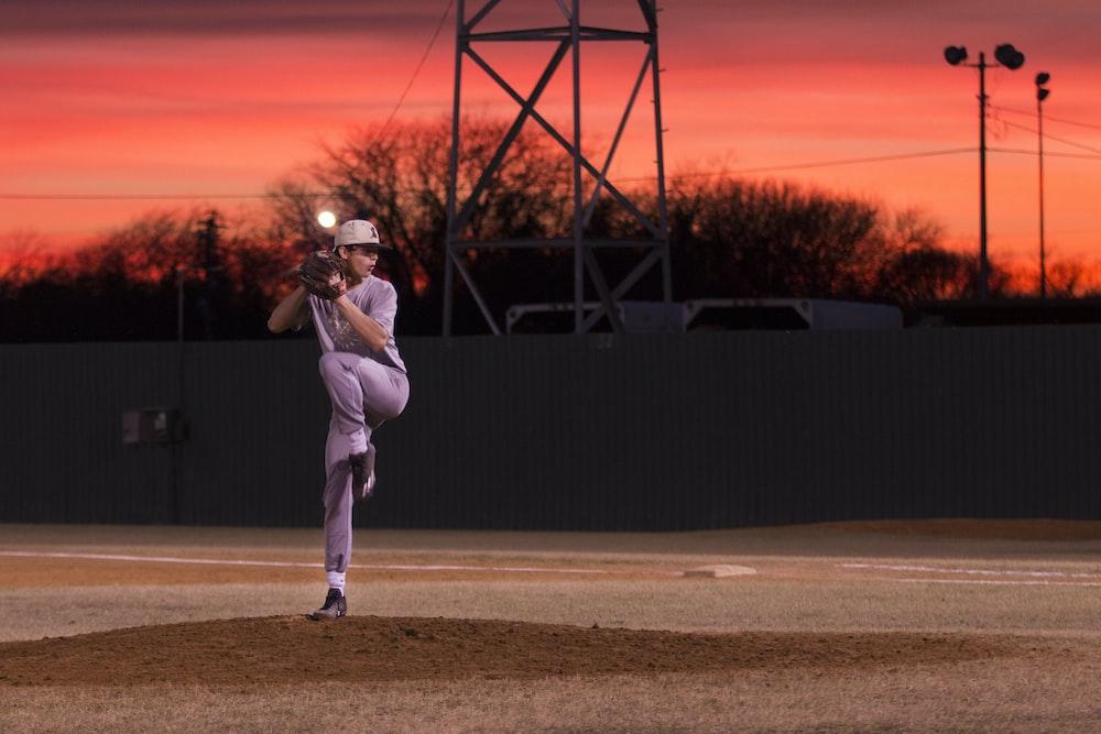 man pitching baseball during sunset