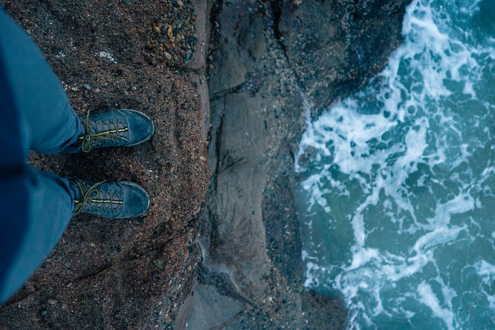 person standing on cliff far from water