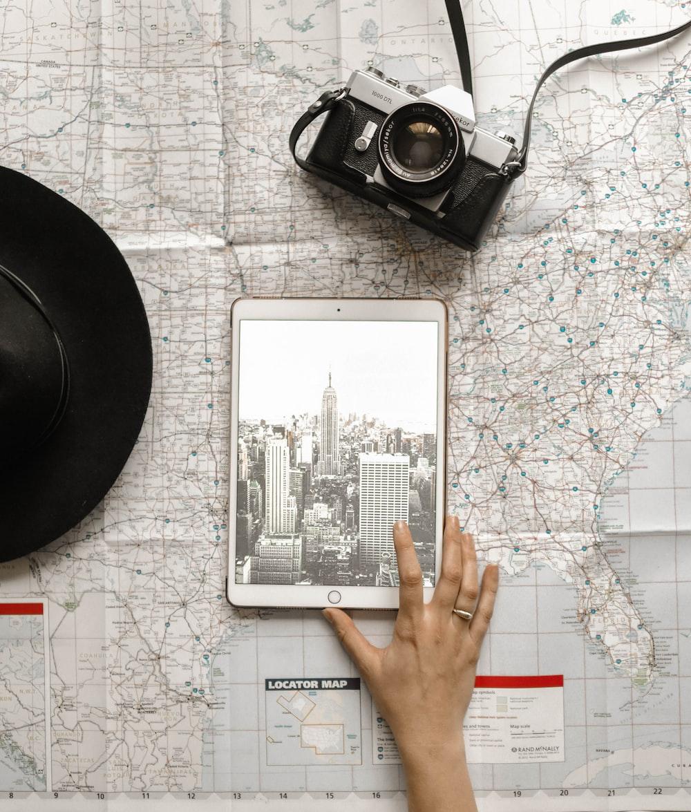 person holding iPad beside SLR camera