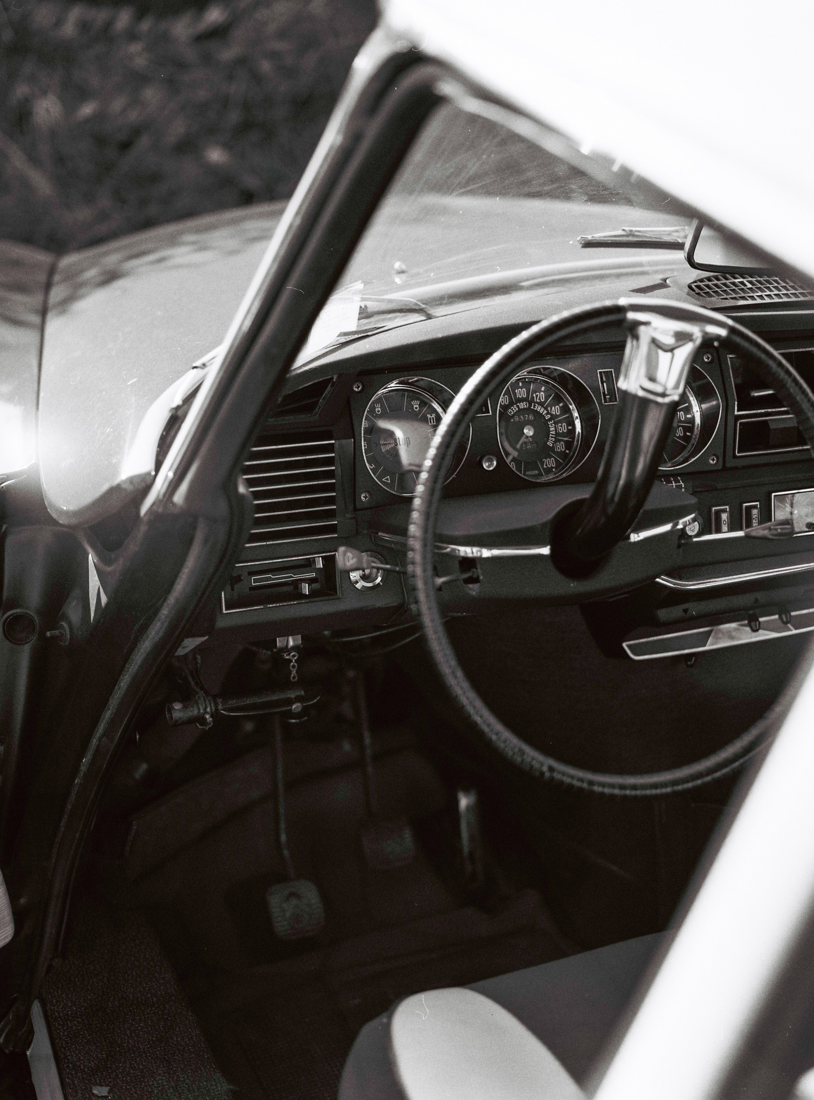 grayscale photo of a vehicle steering wheel