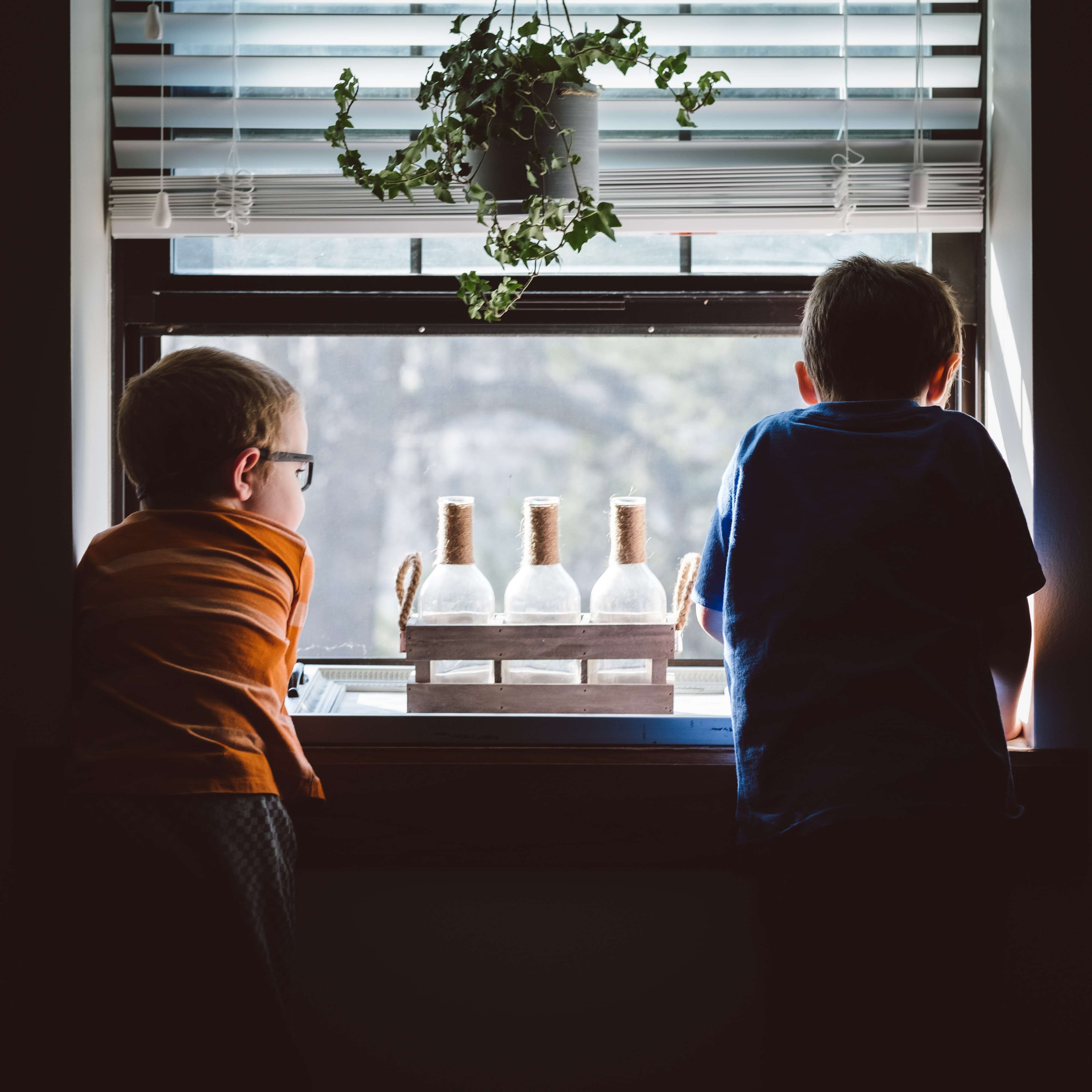 two boys standing in front of window