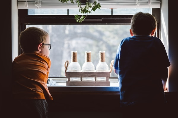 wrath of children two boys standing in front of window