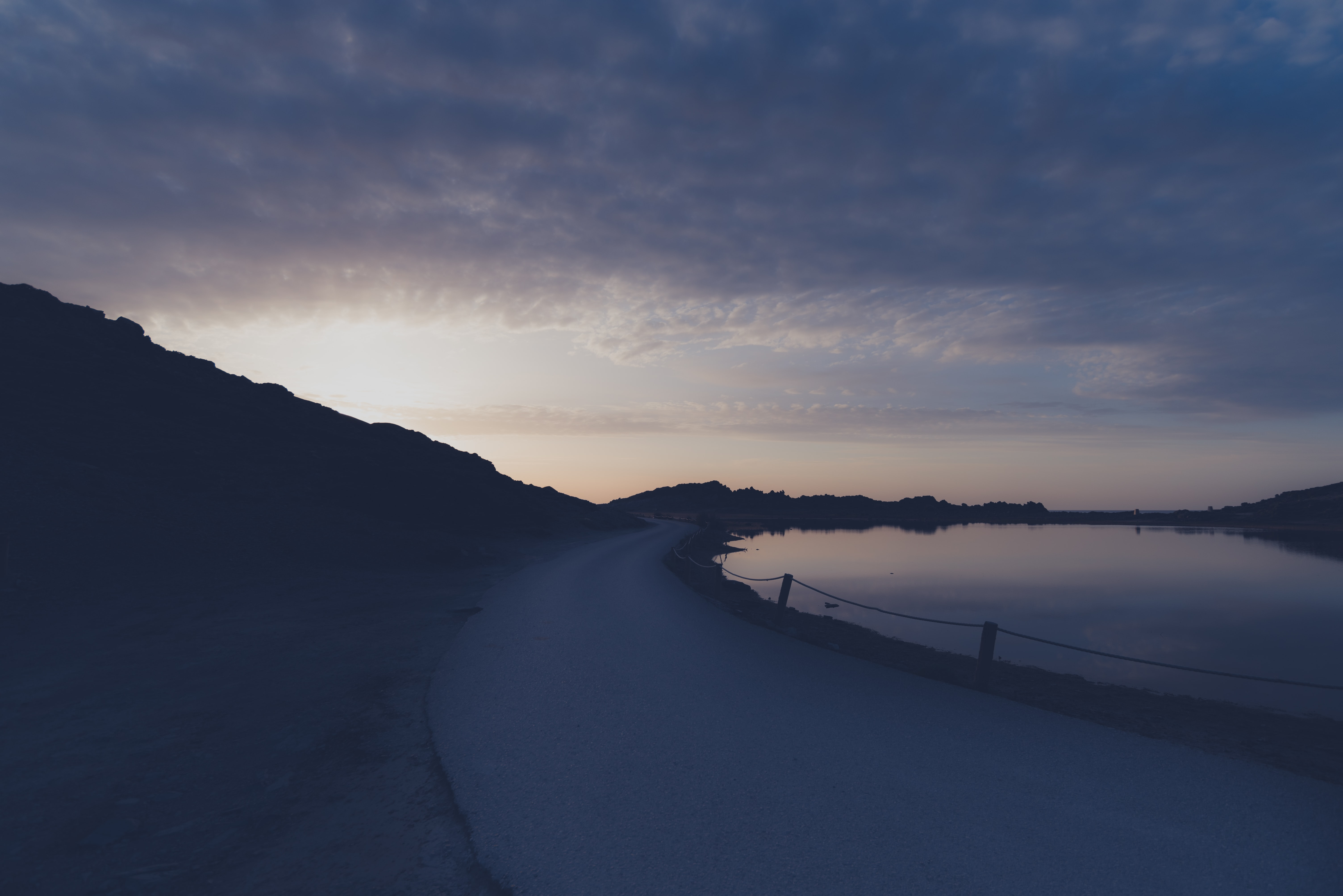 concrete road near body of water during sunrise