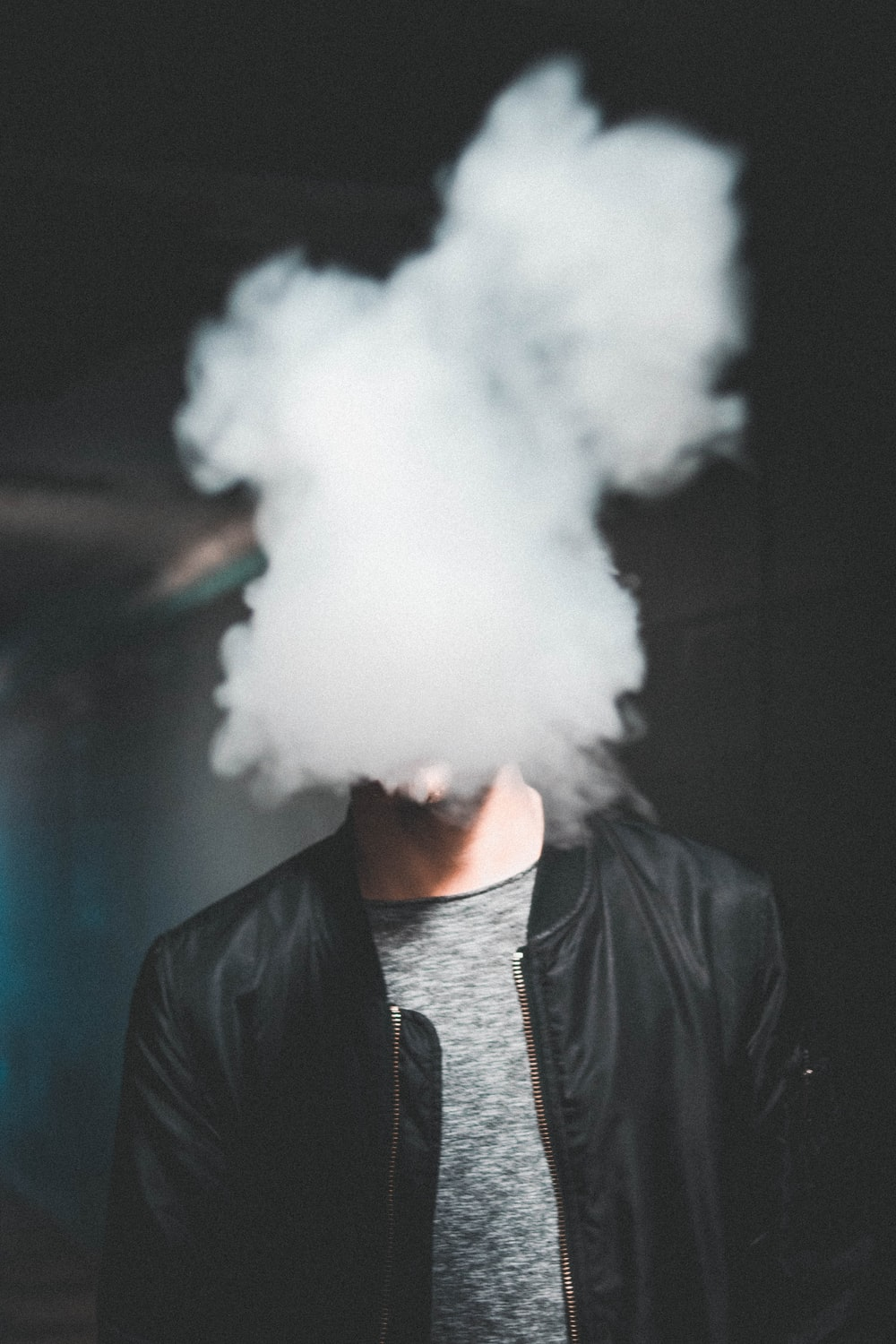 man wearing black leather zip-up jacket while blowing smoke