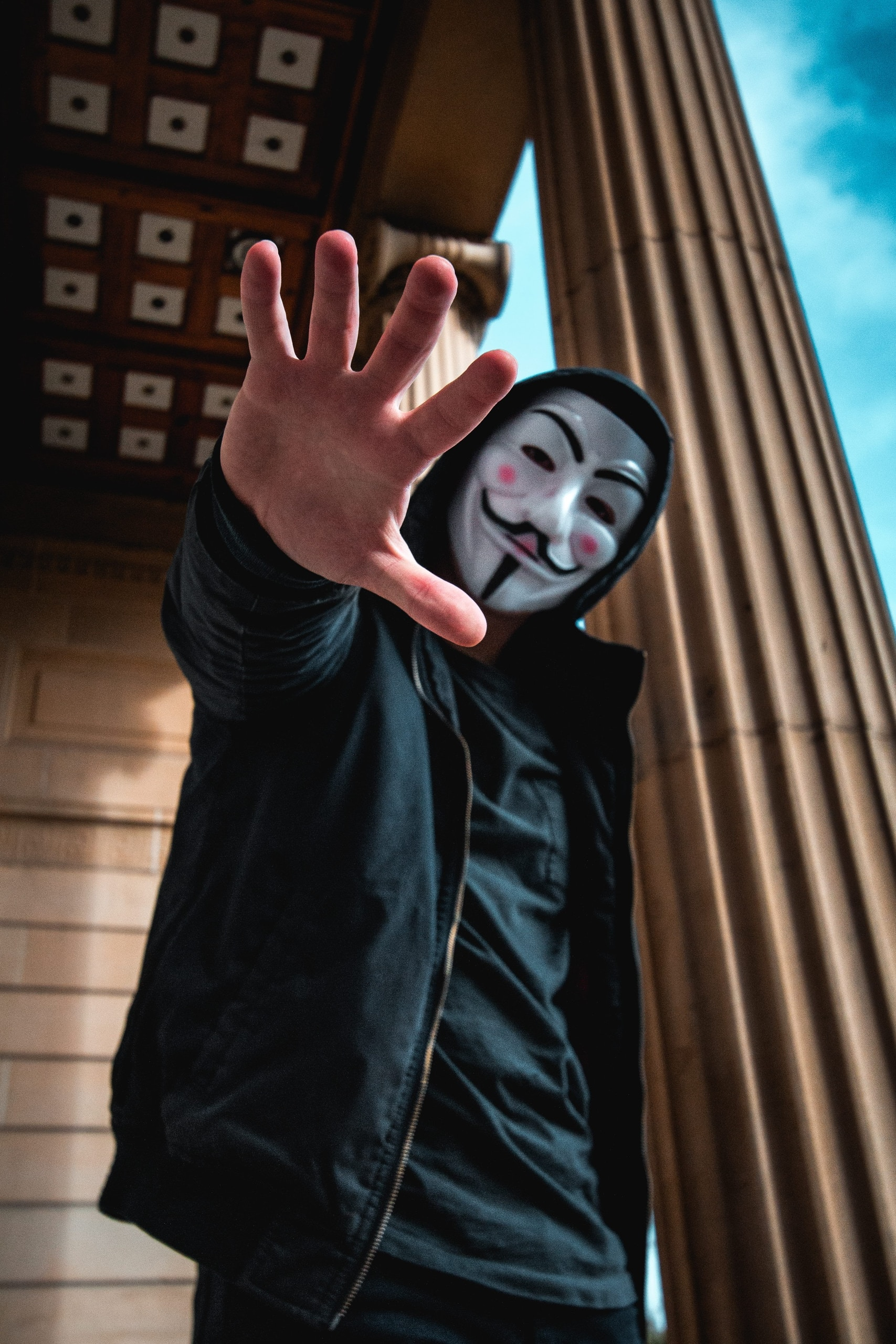 man wearing Guy Fawkes Mask standing inside building