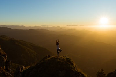 woman stretching on mountain top during sunrise yoga teams background
