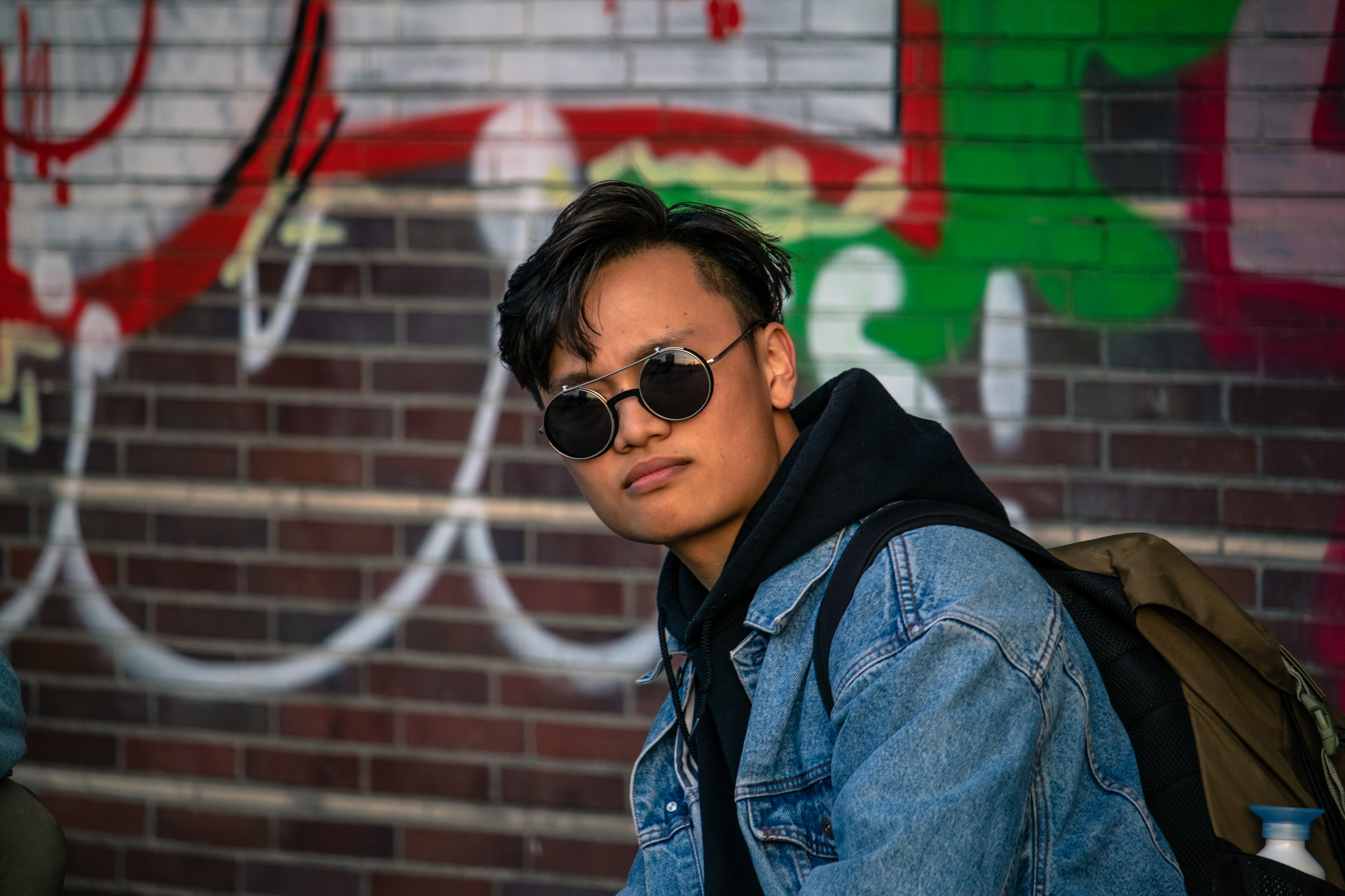 man in black sunglasses and blue denim jacket standing in front of wall