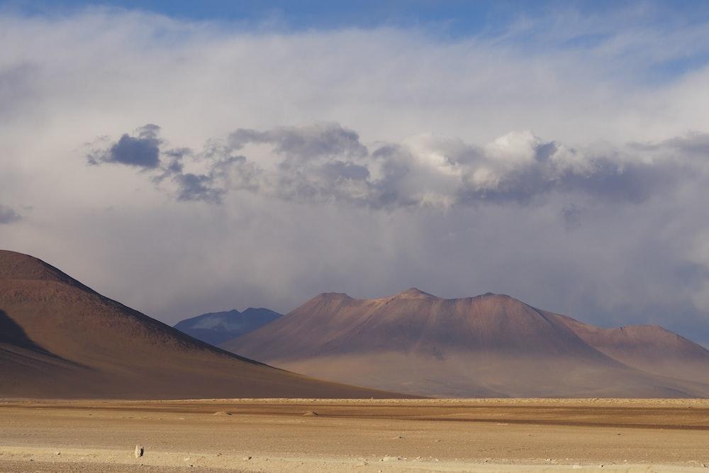 brown mountain beside desert during daytime