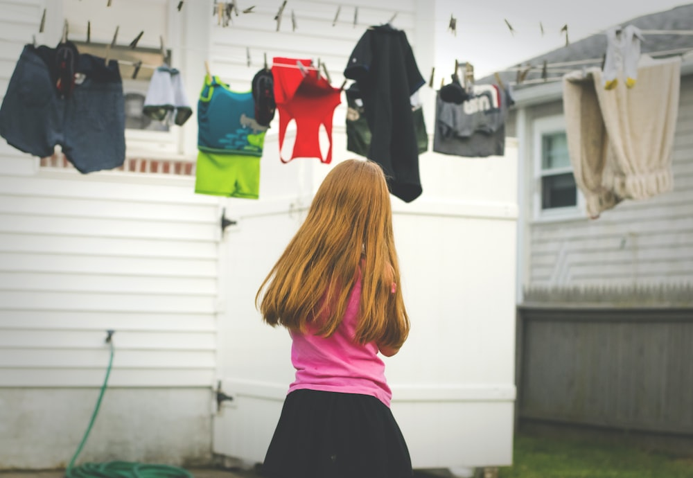 girl standing under clothes on airer at daytime