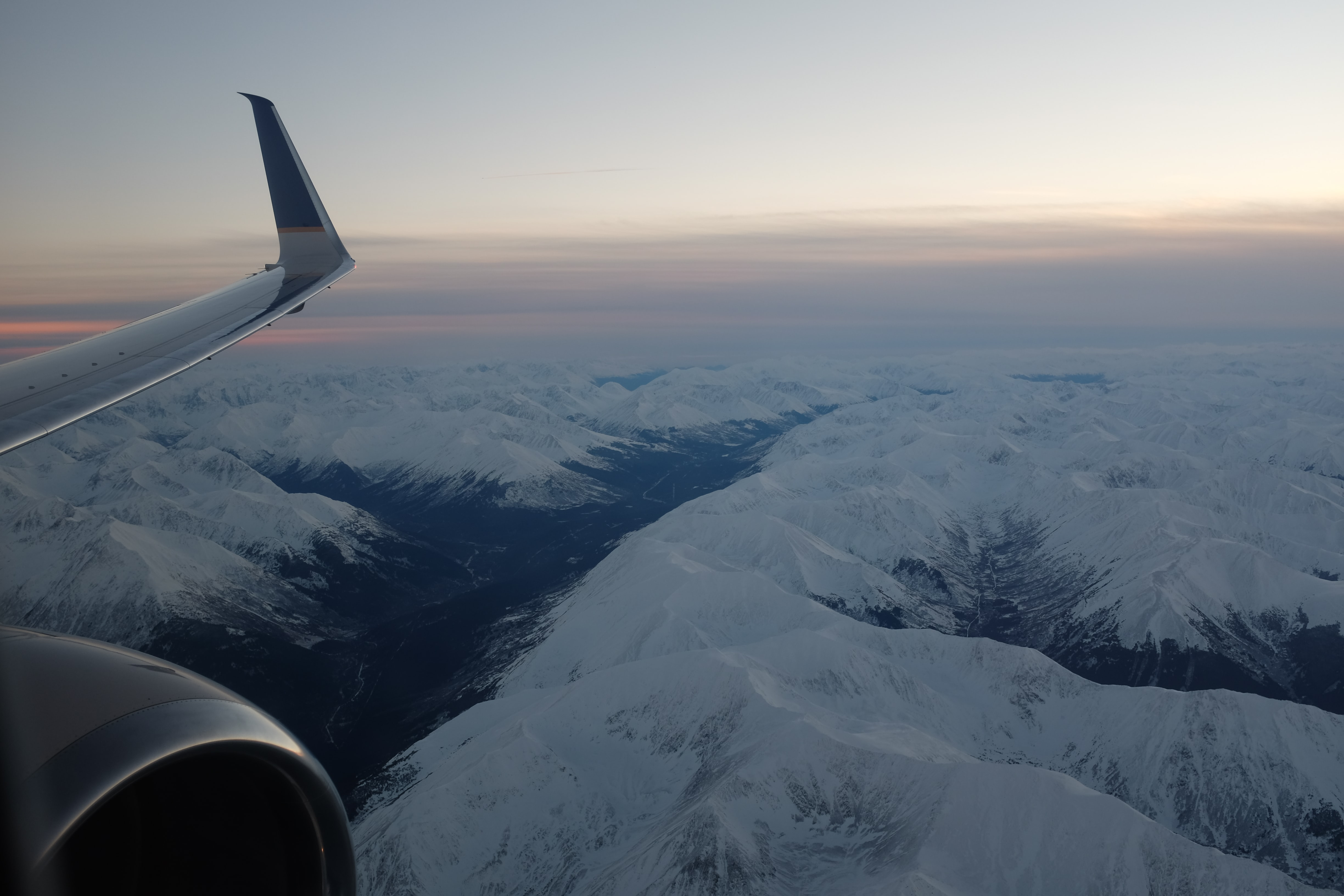 airplane flying above snowy mountains