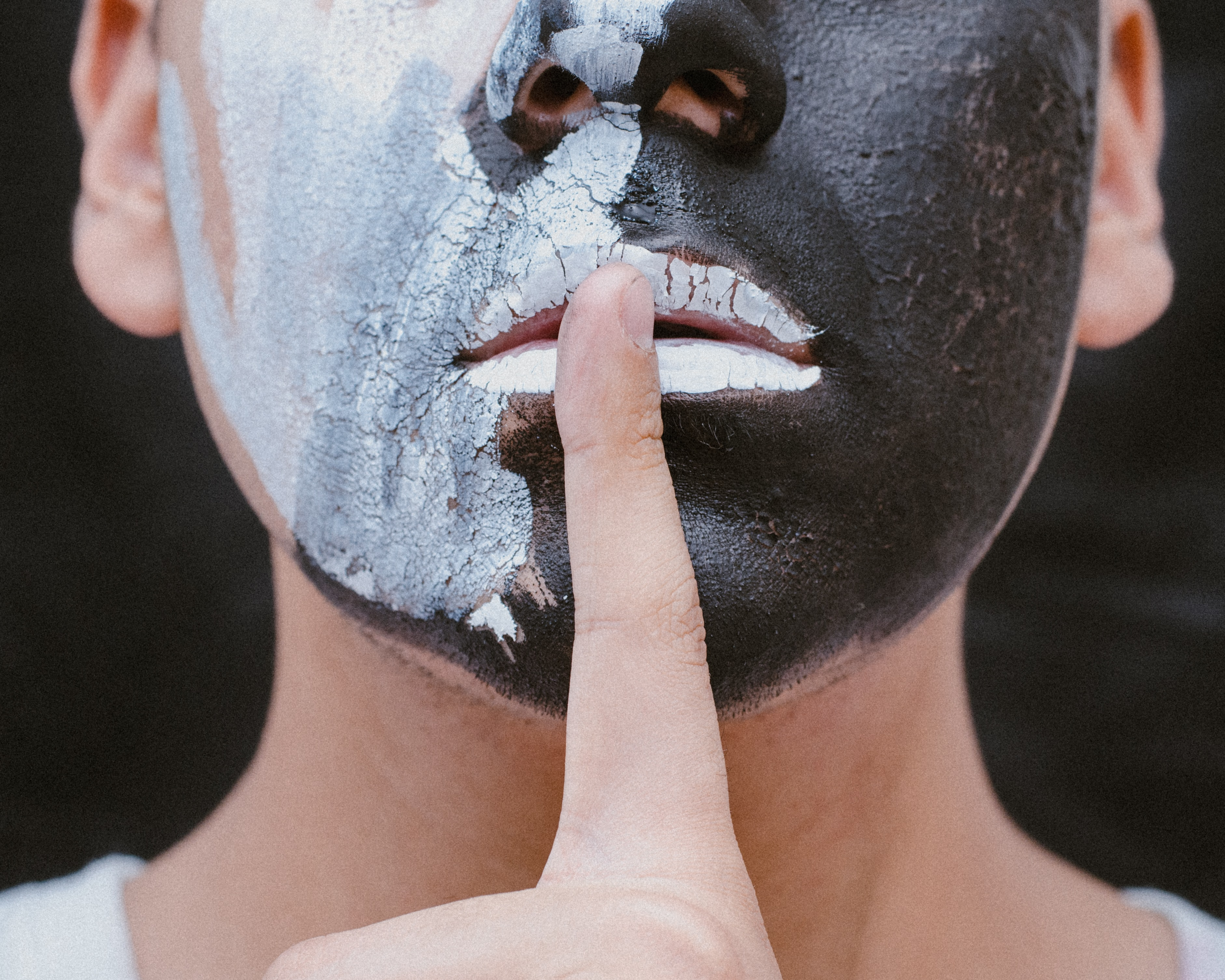 person with black and white face paint with finger on mouth doing the quiet gesture