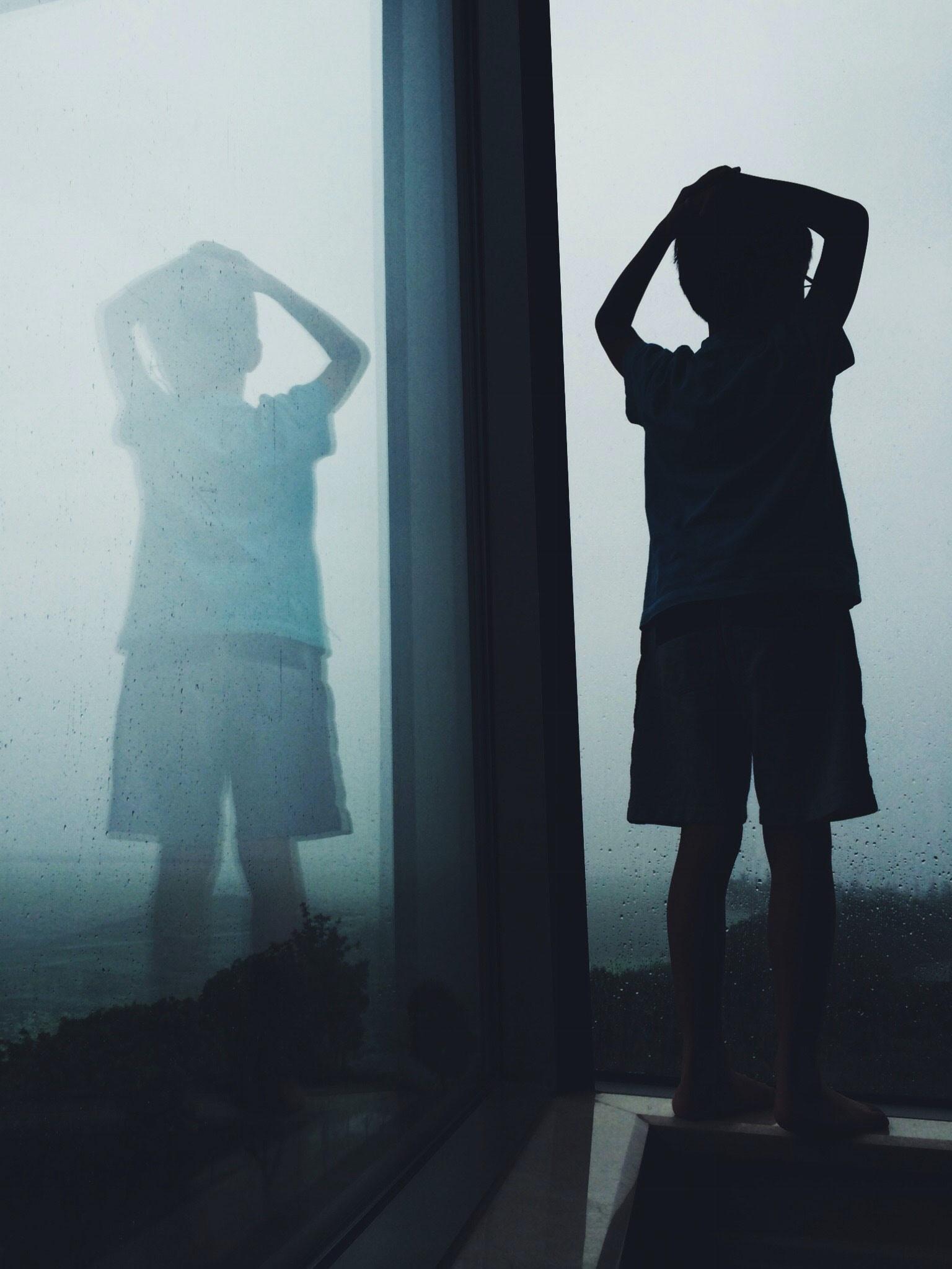 boy near clear glass window