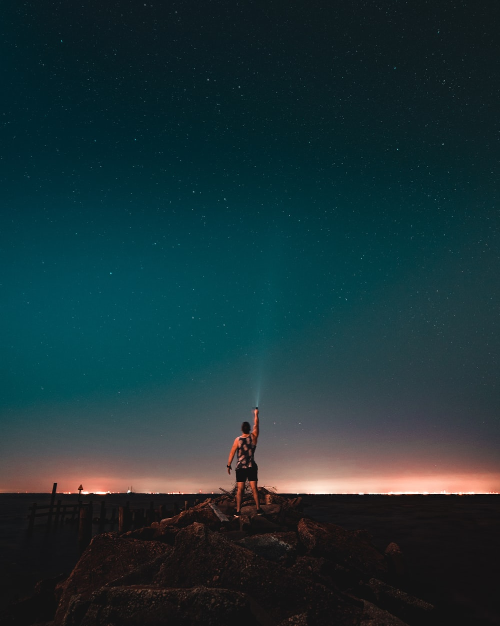 man holding flashlight turned on towards above the sky