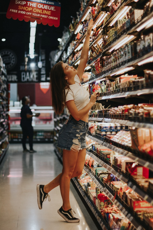 woman standing beside shelf