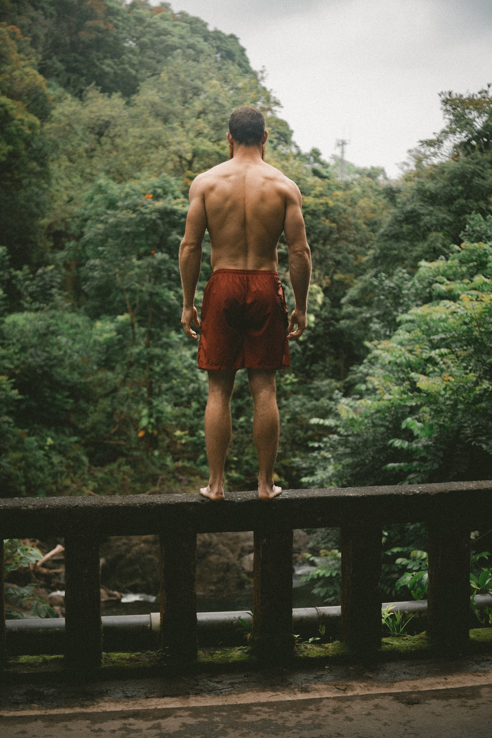 selective focus photography man in red shorts standing on bridge edge