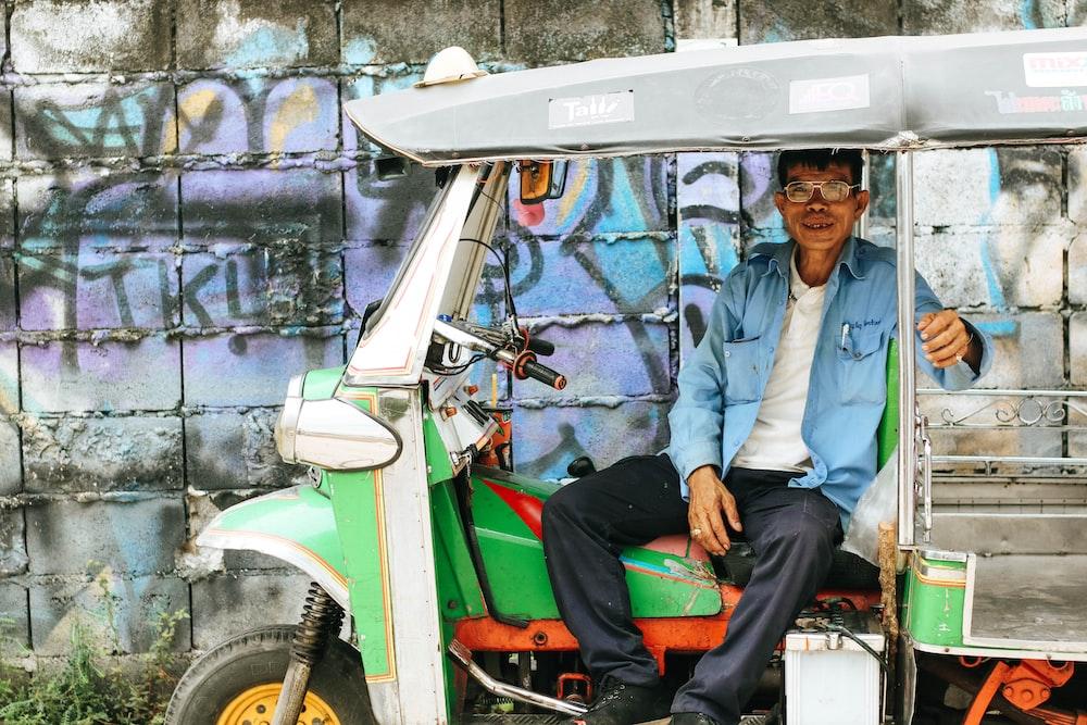 man sitting on auto rickshaw near graffiti wall during daytime