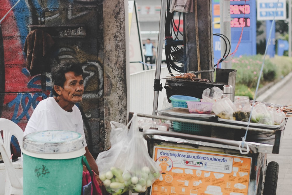 man in white top sitting in front of food stall