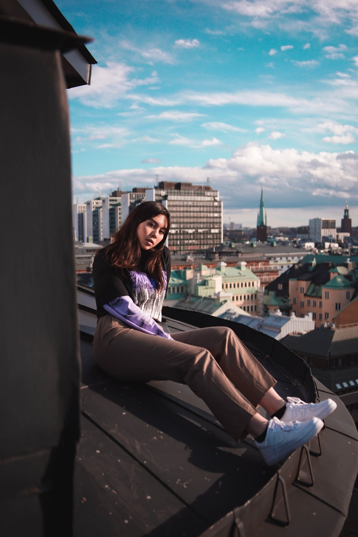 woman sitting near buildings