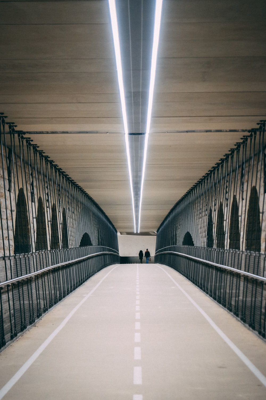 two person walking on bridge