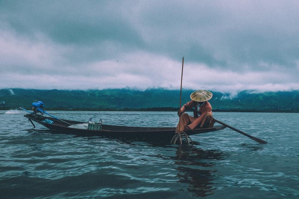 man fishing on boat under dramatic sky