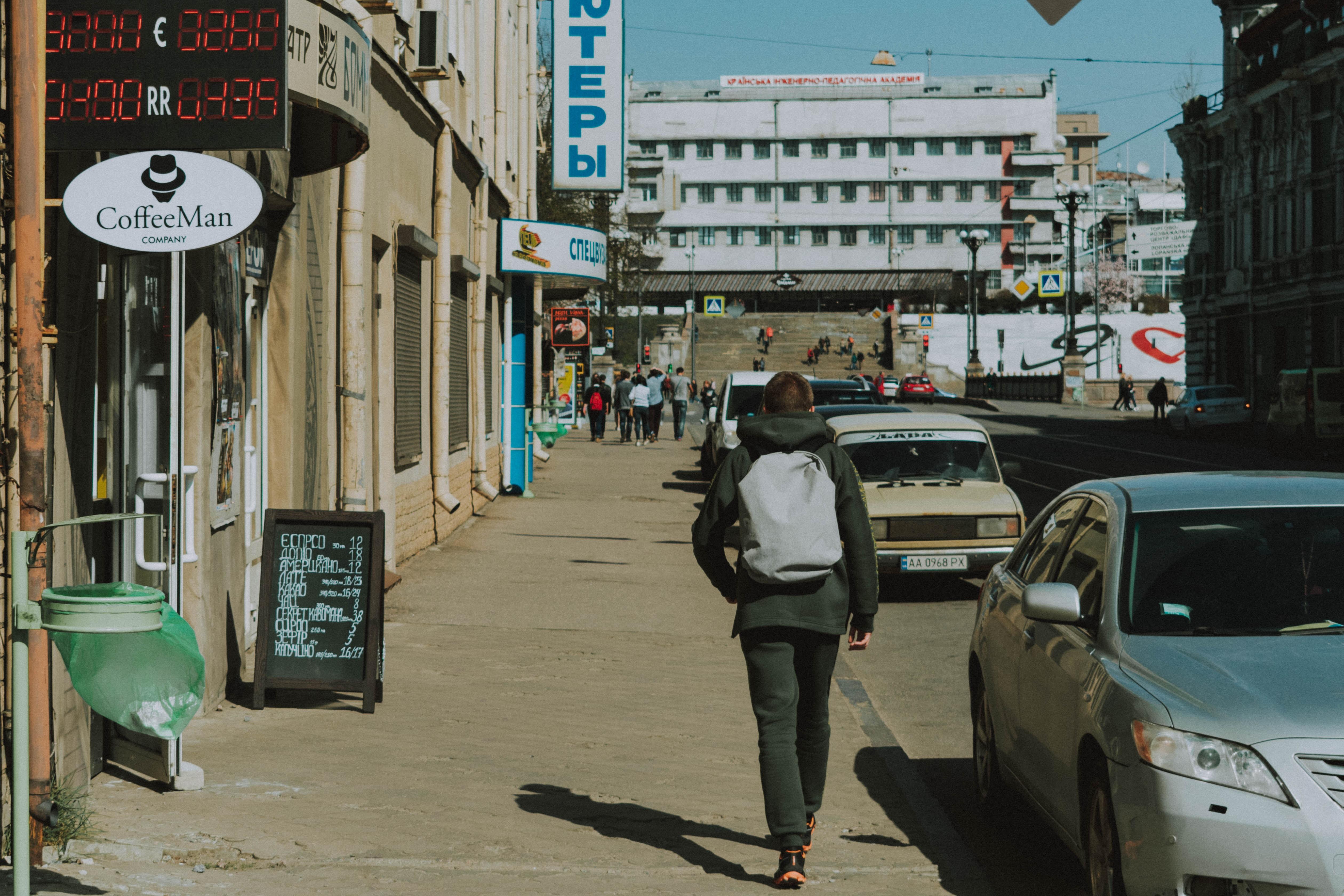 man walking along sidewalk during daytime
