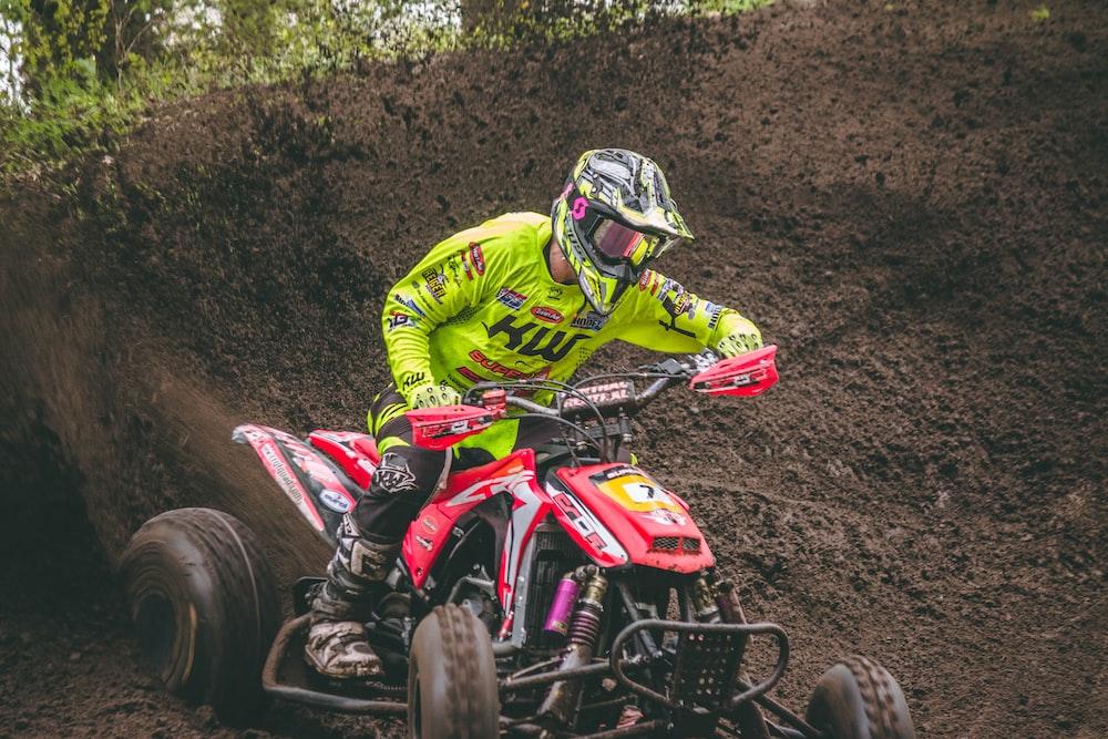 man riding red ATV on ground