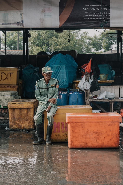 man sitting on yellow fish box during day