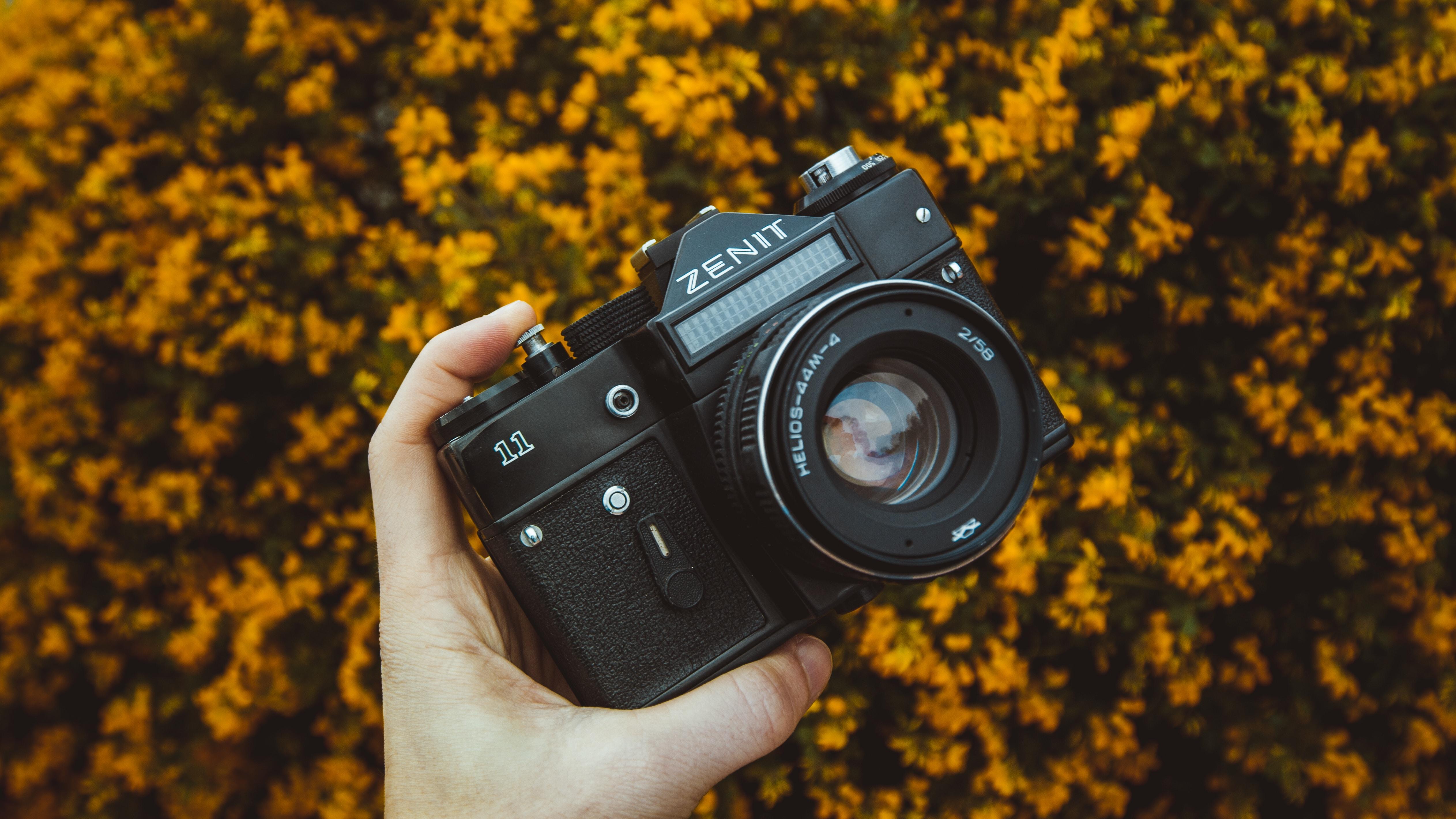 person holding black Zenit camera