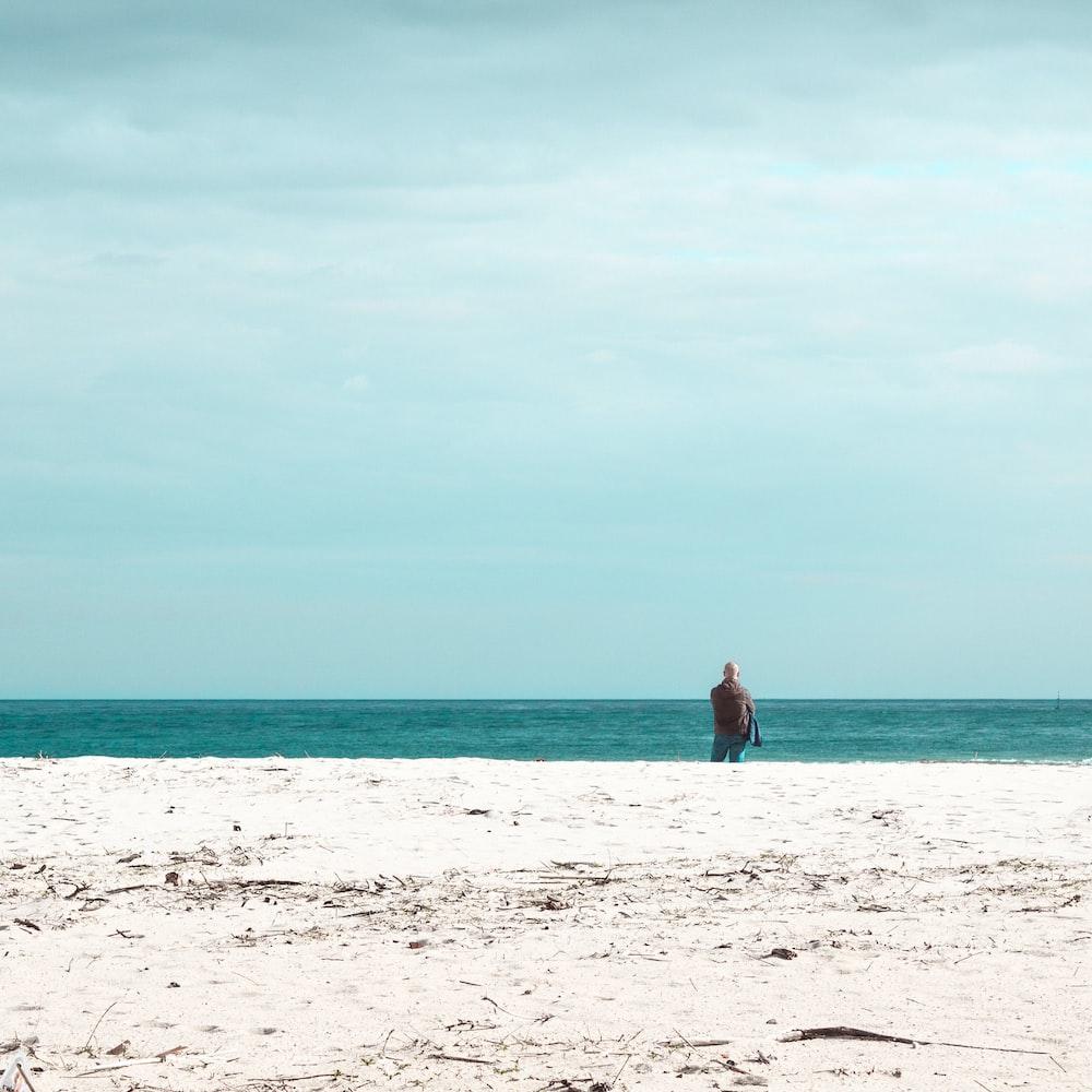 man standing on white sand beach during daytime