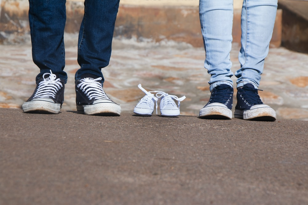 pair of gray low-top shoes between two persons wearing jeans