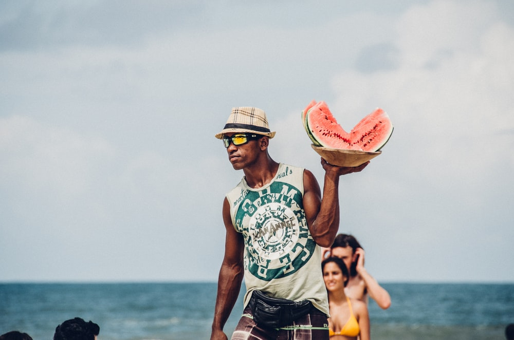 man holding sliced watermelons